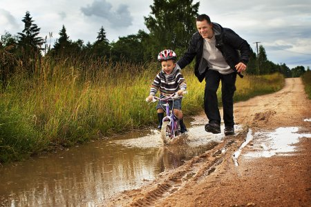 Little boy with Dad on a bike after rain
