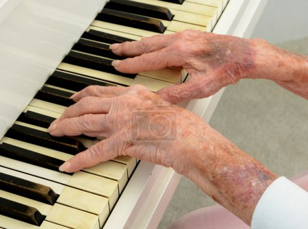 Photo for Closeup image of a very old senior playing piano - Royalty Free Image