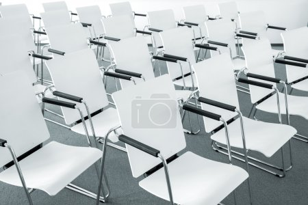Photo pour Rangées de chaises blanches modernes vides dans une salle de conférence - image libre de droit