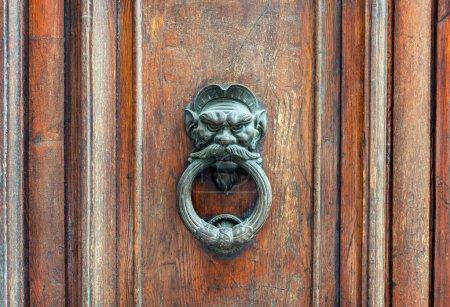 Photo pour Poignée de porte lion de fer sur la vieille porte en bois altérée à Florence, Italie - image libre de droit