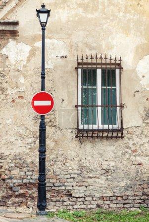 Photo pour Pas de panneau d'entrée accroché au lampadaire sur fond de vieille maison altérée - image libre de droit
