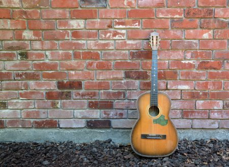 Photo for Guitar player takes a break leaving old acoustic guitar leaning against a red brick wall. - Royalty Free Image