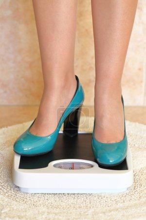 Woman's feet in high heels on bathroom scale