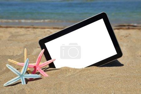 Tablet computer on sandy beach