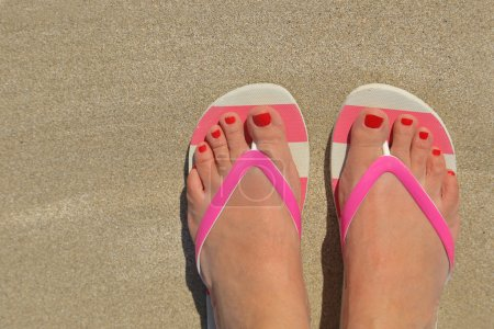 Photo pour Les femmes pieds avec des tongs sur le sable - image libre de droit