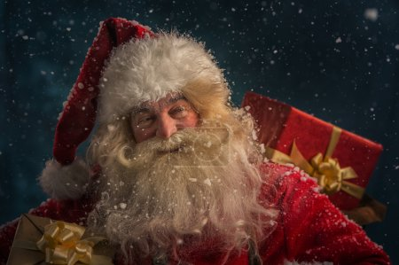 Photo for Photo of happy Santa Claus outdoors under snowfall carrying gifts to children - Royalty Free Image