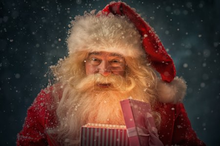 Photo for Photo of kind Santa Claus opening and giving xmas present to camera under snowfall - Royalty Free Image