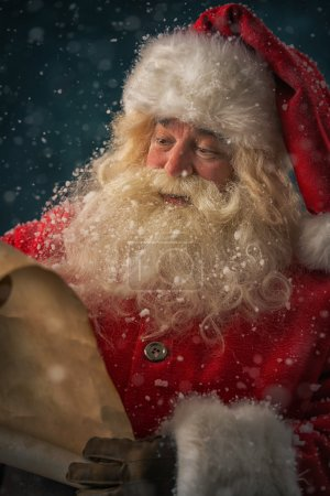 Photo for Portrait of happy Santa Claus reading Christmas letter outdoors at north pole under snowfall - Royalty Free Image