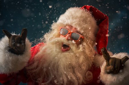 Photo for Santa Claus wearing sunglasses dancing outdoors at North Pole in snowfall. He is celebrating Christmas after hard work - Royalty Free Image