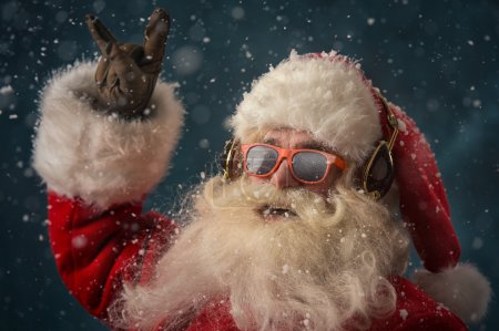 Photo pour Le Père Noël écoute de la musique dans les écouteurs portant des lunettes de soleil. Noël . - image libre de droit