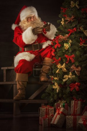 Photo for Santa Claus decorating Christmas tree in dark room - Royalty Free Image