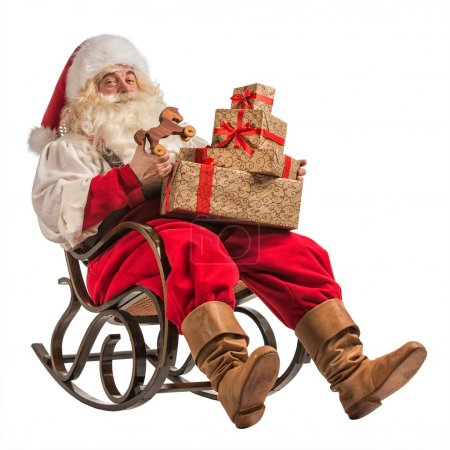 Photo for Santa Claus sitting in rocking chair with gifts isolated on white background - Royalty Free Image