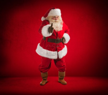 Photo for Happy Christmas Santa Claus showing thumb up. Red background. Full length - Royalty Free Image