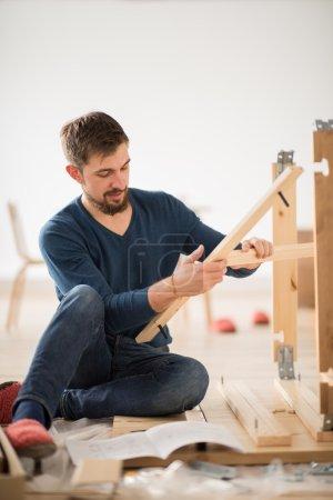 Photo pour Homme, assembler des meubles d'auto-assemblage dans Maison Neuve - image libre de droit
