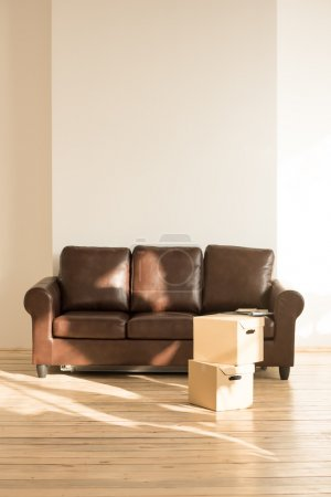 Sofa and cardboard boxes in new home