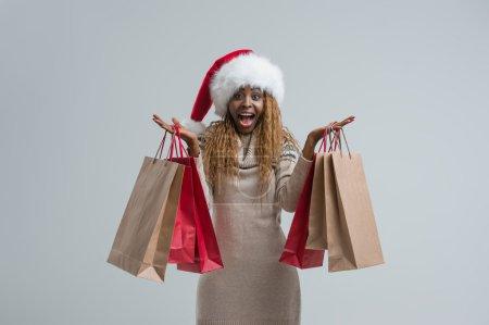 Photo pour Joyeux shopping femme de Noël portant le chapeau du Père Noël avec des sacs fond gris - image libre de droit