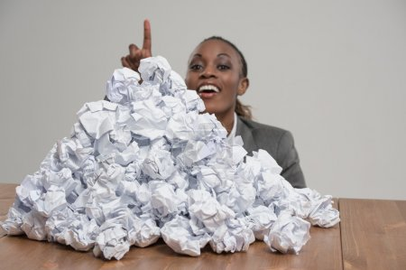Photo for African business woman with crumpled pile of papers at workplace at office - Royalty Free Image