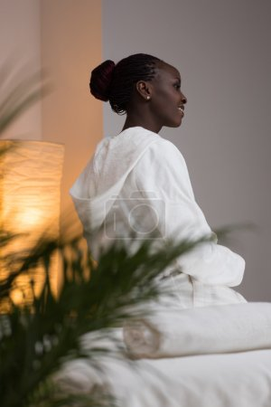 Photo for Young pretty african woman sitting at beauty spa salon wearing bathrobe - Royalty Free Image