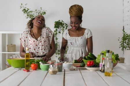 Photo for Two african women cooking in kitchen making healthy food salad with vegetables - Royalty Free Image
