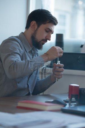 Businessman filling electronic cigarette