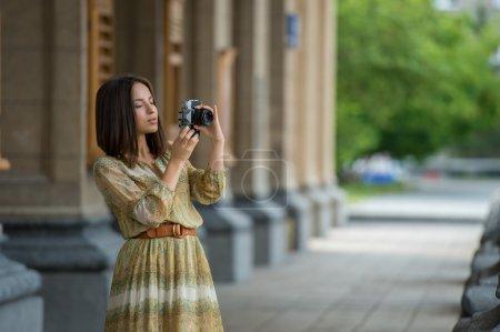 Photo pour Fille voyageur heureux faisant photo de bâtiment historique avec caméra rétro sur la rue de la ville - image libre de droit