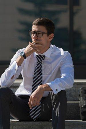 Well dressed businessman smoking