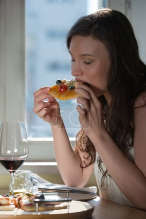 Woman eating  pizza and drinking wine