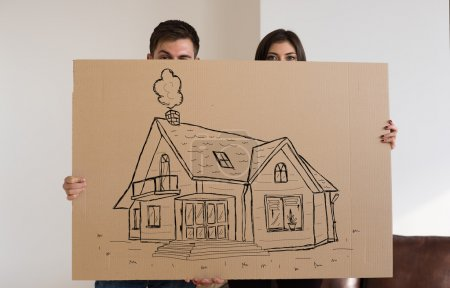 Photo for Couple hiding behind cardboard sign with new house. Mortgage and credit concept. - Royalty Free Image