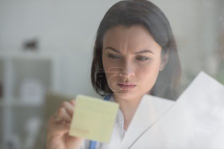 Doctor writing on transparent board