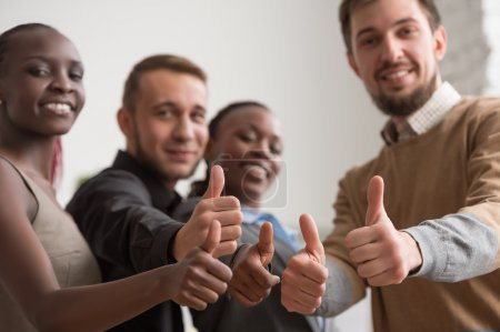 Photo for Cheerful business group giving thumbs up in office - Royalty Free Image