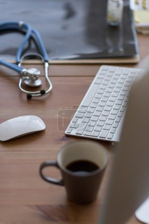 Computer, a stethoscope and a cup