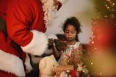 Santa Claus with cute african girl
