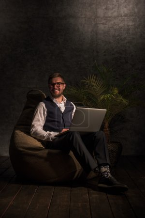 Photo for Business man Working on Laptop at home or office while sitting on beanbag - Royalty Free Image