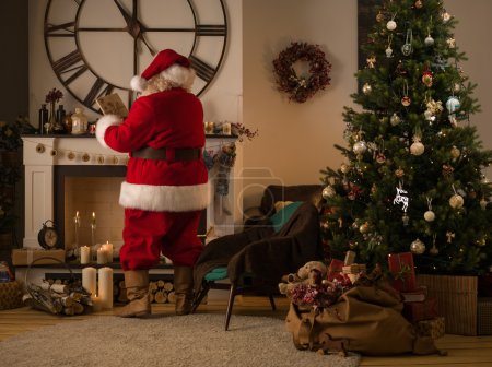Photo for Santa Claus Putting Gifts in Socks on Fireplace at Home - Royalty Free Image