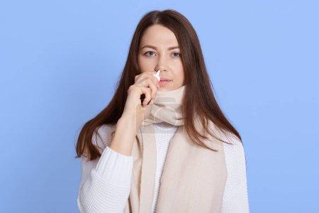Junge dunkelhaarige Frau mit weißem Pullover und Schal steht tropfnasentropfen isoliert auf blauem Hintergrund, kranke Dame blickt mit aufgeregtem Gesichtsausdruck in die Kamera.