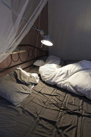 Disheveled sheets and pillows of an unmade bed,led...