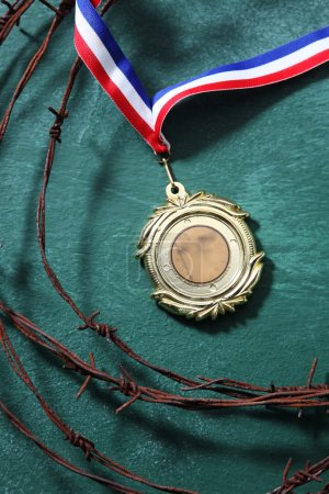 medal surrounded by the barbwire