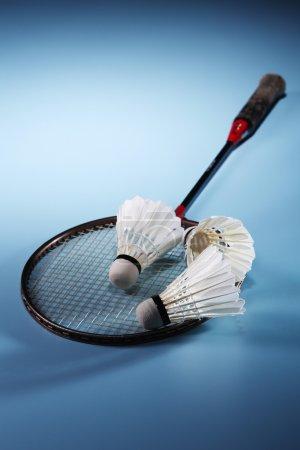 Photo pour Gros plan d'une raquette de badminton avec des Shuttlecocks sur fond bleu - image libre de droit