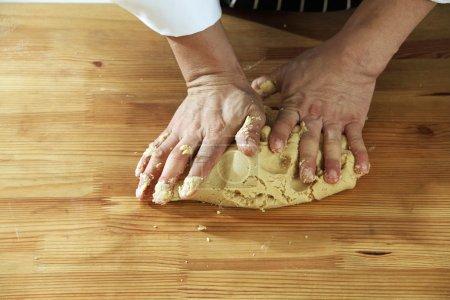 Photo pour Mains dans la farine gros plan pétrissage pâte sur la table - image libre de droit