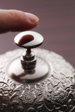 Hand pressing a service bell