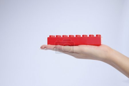 female hand holding a plastic block