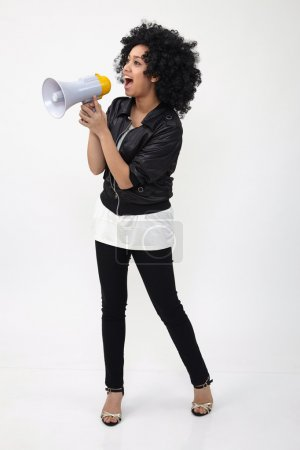Photo for Indian teenage holding a megaphone on the white background - Royalty Free Image