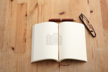 Photo for Blank notepad with spectacles on wooden table. Above view. - Royalty Free Image