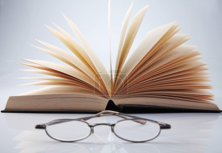 Fanned book with glasses
