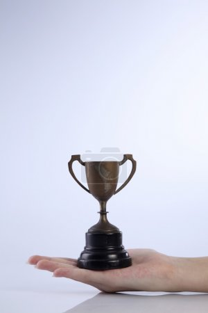 Female hand with trophy bowl