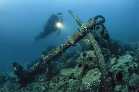 Diver and old ship anchor