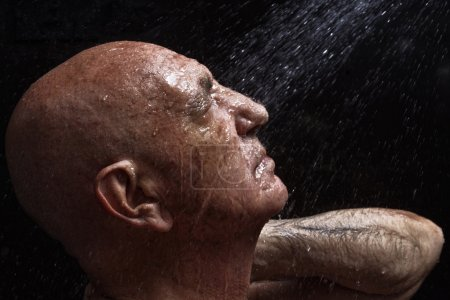 portrait of a bald old man showering