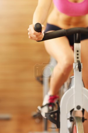 Midsection of sporty group of woman on spinning cl...