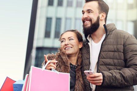 Photo pour Photo de jeune couple avec sacs à provisions dans la ville - image libre de droit