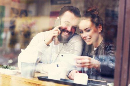Happy couple using phones